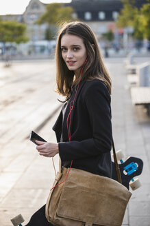 Young woman with longboard and cell phone in the city on the move - UUF15651