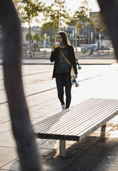 Young woman with longboard having a snack in the city - UUF15657