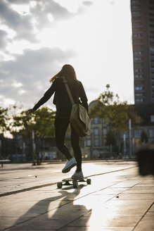 Rear view of young woman riding longboard in the city - UUF15663