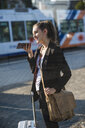 Smiling young woman with luggage at tram station in the city using cell phone - UUF15666