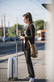 Young woman with luggage at tram station in the city using cell phone - UUF15669
