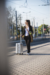 Young woman with luggage at tram station on the move - UUF15672