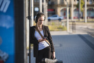 Young woman with headphones and cell phone at tram station - UUF15675