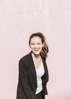 Portrait of laughing young woman in front of pink wall - UUF15681