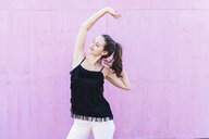 Smiling young woman stretching in front of pink wall - UUF15684