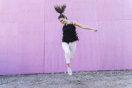 Exuberant young woman jumping in front of pink wall - UUF15690