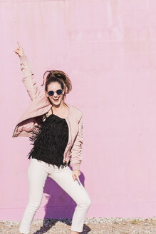 Happy young woman gesturing in front of pink wall - UUF15699