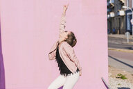 Happy young woman moving in front of pink wall - UUF15702