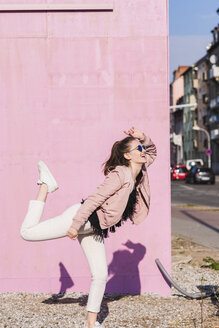 Happy young woman moving in front of pink wall - UUF15705