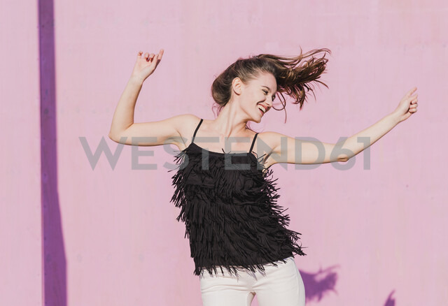 Happy young woman moving in front of pink wall - UUF15711