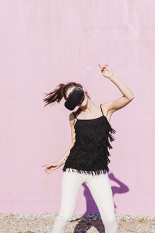 Young woman wearing VR glasses moving in front of pink wall - UUF15714