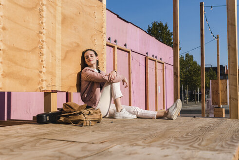 Relaxed young woman sitting on platform next to guitar case and bag - UUF15723