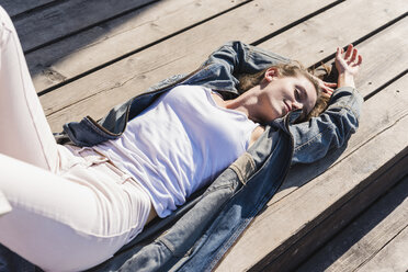 Relaxed young woman lying on wooden boards in sunshine - UUF15747