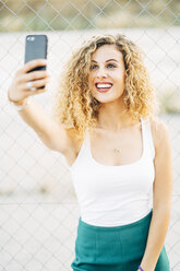 Portrait of blond young woman taking selfie with mobile phone - OCMF00015