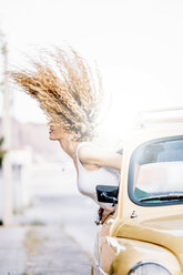 Young woman leaning out of car window tossing her hair - OCMF00018