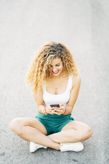 Smiling young woman sitting on street looking at mobile phone - OCMF00021