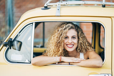 Portrait of happy blond woman looking out of window of classic car - OCMF00024