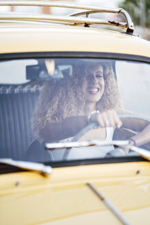 Portrait of laughing blond woman driving classic car - OCMF00027