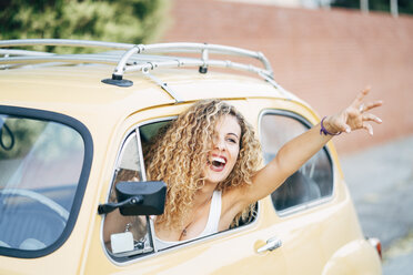 Portrait of happy blond woman leaning out of window of classic car showing victory sign - OCMF00030