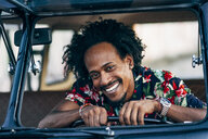 Portrait of laughing man looking out of car window - OCMF00036