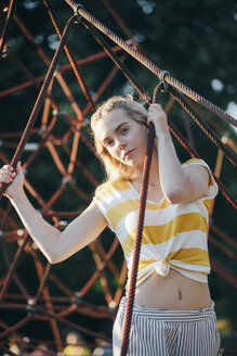 Portrait of young woman at climbing frame - JESF00186