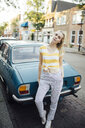 Portrait of young woman standing in front of vintage car - JESF00189