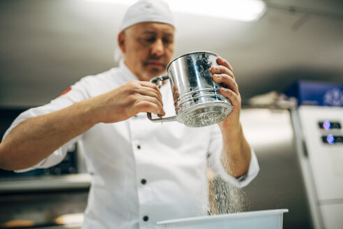 Baker working with flour sifter in bakery - OCMF00045