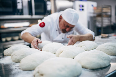 Baker working with dough in bakery - OCMF00048