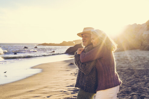 Side view of happy mature woman embracing senior man standing at beach on sunny day - TGBF00857
