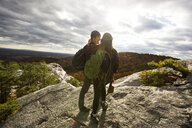 Full length of active couple with backpacks hiking on mountain cliff against cloudy sky - TGBF00884