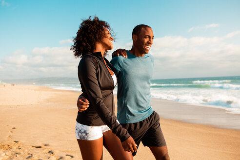 Cheerful  couple in sportswear walking at beach on sunny day - TGBF00905