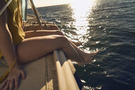 Couple sitting on sailboat in sea during summer vacation - TGBF00911