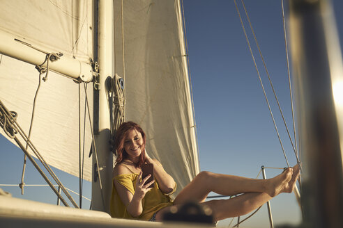 Happy woman taking selfie through smart phone while sitting on sailboat - TGBF00917