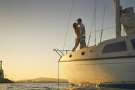 Side view of romantic couple kissing while standing on sailboat during sunset - TGBF00920