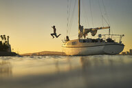 Woman looking at man jumping in sea from sailboat against clear sky during sunset - TGBF00923