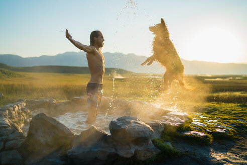 Dog Jumping Towards Man Standing In Hot Spring - TGBF00944