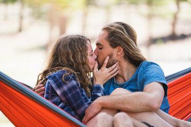 Man And Woman Kissing While Sitting On Hammock - TGBF00971