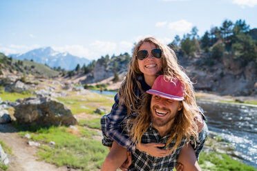 Hiker Giving Piggyback Ride To Woman By River In Forest - TGBF00974