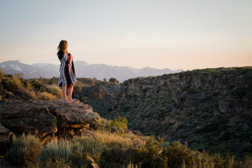 Woman Wrapped In Blanket Standing On Cliff Against Sky - TGBF00983