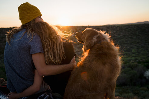 Dog Looking At Couple Embracing On Mountain During Sunset - TGBF00986