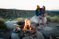 Loving Hikers Sitting On Rock By Campfire - TGBF00992