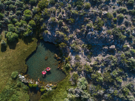 Overhead view of couple floating on inflatable rings in lake - TGBF01001