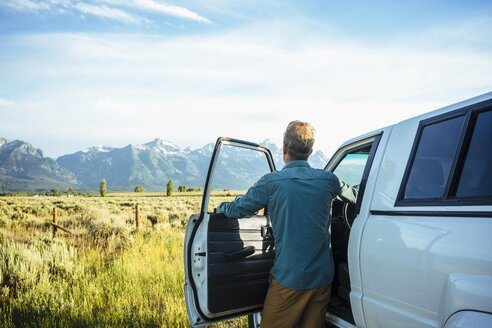 Rear view of young man standing by car while looking at mountains in Grand Teton National Park - TGBF01007