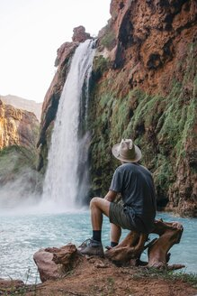 Rear view of young male tourist looking at Havasu Falls in Grand Canyon National Park - TGBF01016