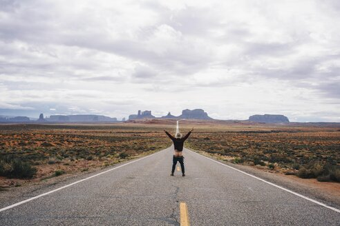 Full length rear view of young man  standing on desert highway leading towards Monument Valley - TGBF01022