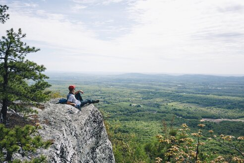 Young male hiker relaxing on mountain cliff against sky - TGBF01028