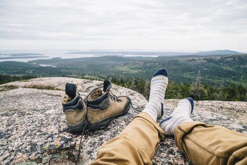 Male hiker relaxing on rocky mountain overlooking Acadia National Park - TGBF01034