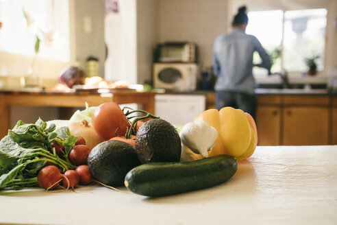 Variety of fresh vegetables on table with woman cooking in background at home - TGBF01040