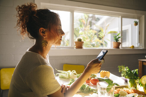 Side view of young woman using mobile phone at dining table - TGBF01058