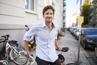 Portrait of smiling young man with racing cycle in the city - PNEF01082
